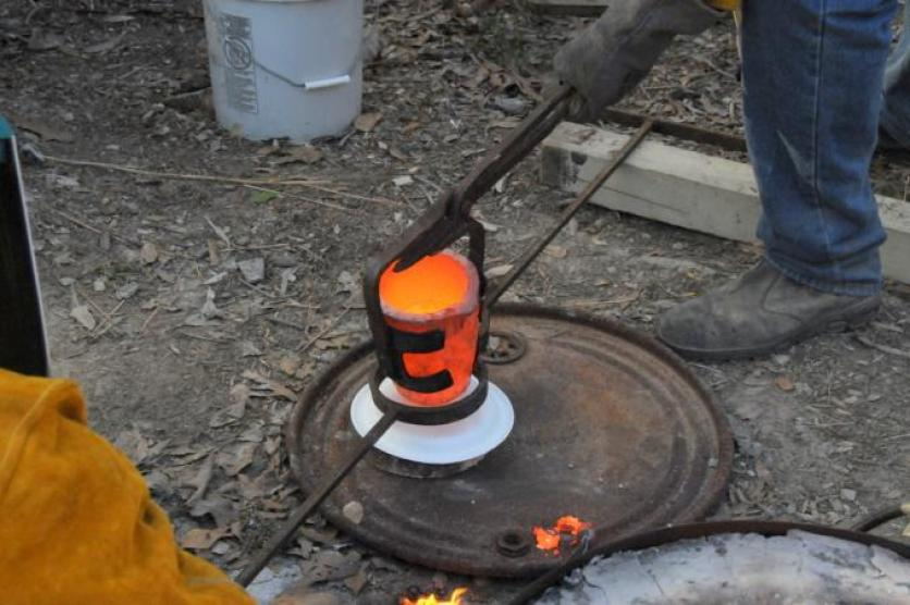 Bronze crucible being transferred to pouring shank