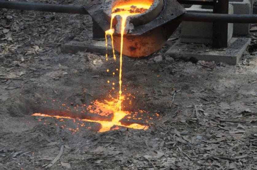 Pouring an Iron Cross in a mold carved in the ground.